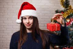 Young cute disappointed woman in Santa cap discontented with a g. Ift. New Year, Christmas, gift, surprise, celebration, emotions concept royalty free stock image