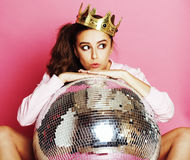 Young cute disco girl on pink background with disco ball and cro. Wn smiling adorable emotions royalty free stock image