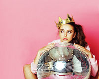 Young cute disco girl on pink background with disco ball and cro Stock Image