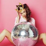 Young cute disco girl on pink background with disco ball and crown Royalty Free Stock Photography