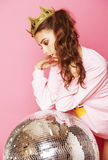 Young cute disco girl on pink background with disco ball and crown Royalty Free Stock Photos