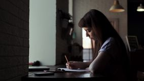 Young cute female artist sits at the table and draws in a notebook stock footage