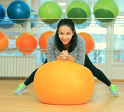 Young cute female with fit ball in sport center Royalty Free Stock Photography