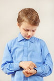 Young cute gentleman fastened buttons on sleeve his bright shirt Stock Images