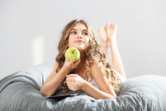 Young cute girl with apple Royalty Free Stock Images