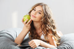 Young cute girl with apple Royalty Free Stock Photos