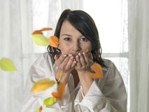 Young cute girl blowing colorful bird feathers. In front of windows royalty free stock photos