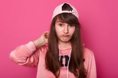 Young cute girl in casual clothes rose hoodie and visor cap back, posing on pink background looking at camera with pouty lips, has stock photo