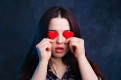 Young cute girl covering eyes with fabric hearts, studio shoot. Love, emotions concept Royalty Free Stock Photography