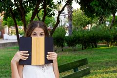 Young cute girl is covering her face with a book. Surprised and shocked woman. Emotional girl holding a book in her hands on the royalty free stock image