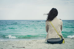 Young cute girl with curly hair sitting on an empty beach. And looks at sea. Outdoors is cold and she is wearing a beige jacket, blue jeans and a striped t Stock Images