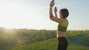 Young cute girl doing gymnastics at sunset. The athlete performs exercises with a fitness elastic band. Steadicam shot stock footage