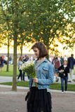 Young cute girl with flowers received the message or call on her. Smartphone, waiting for meeting with friend or date with her boyfriend on the opening the art Stock Photo
