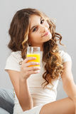 Young cute girl with glass of orange juice Stock Photography