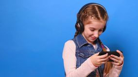 Young cute girl in headphones playing the video game on her smartphone stock video