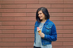 Young cute girl holding an ice cream cone with jam in her hand. Woman on a brick wall background on the street in a denim jacket Stock Photography