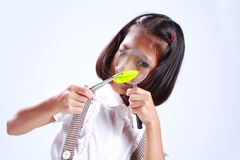 Young cute girl holding magnifying stock photography