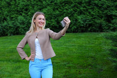 Young cute girl holding phone at arm`s length and directs smiles Stock Image