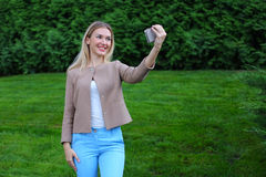 Young cute girl holding phone at arm`s length and directs smiles Royalty Free Stock Images
