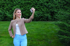 Young cute girl holding phone at arm`s length and directs smiles Royalty Free Stock Image
