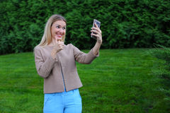 Young cute girl holding phone at arm`s length and directs smiles Stock Photo