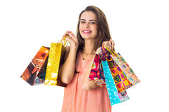 Young cute girl keeps in two hands shopping bags. And smiling Royalty Free Stock Image