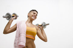 Young cute girl lifting weights and smiling Royalty Free Stock Image