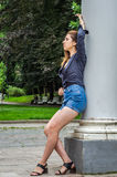 Young cute girl with long hair in a shirt and denim shorts walking in the park in Lviv Striysky sunny summer day posing near the c Royalty Free Stock Image