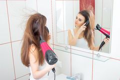 Young cute girl looks in the mirror and and drying long hair Royalty Free Stock Photo