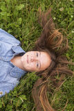 Young cute girl lying on green grass, top view. Walk. Royalty Free Stock Photography