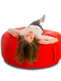 Young cute girl lying on round shape red beanbag chair Royalty Free Stock Images