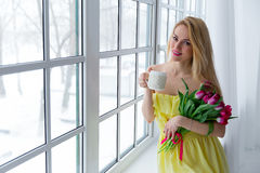 Young cute girl with pink tulip bouquet. Royalty Free Stock Image