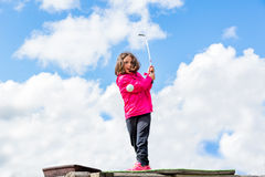 Young cute girl playing golf, low angle view with clouds in background. Royalty Free Stock Image
