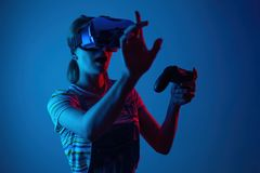 Young cute girl playing vr. with creative blue-red light. it is emeanantly and fun royalty free stock photo