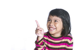 A young cute girl is pointing in the corner. She also looks there and smiles.  over white. Royalty Free Stock Photos