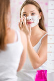Young cute girl putting facial mask on her face Royalty Free Stock Images