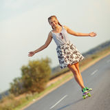 Young cute girl rides skateboard on road Stock Images