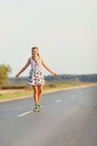 Young cute girl rides skateboard on road Royalty Free Stock Image