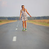 Young cute girl rides skateboard on road Stock Photography
