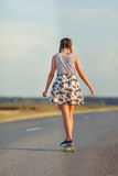 Young cute girl rides skateboard on road Stock Photo