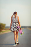 Young cute girl rides skateboard on road Royalty Free Stock Photos