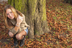 Young cute girl sitting in the autumn forest or Park. Stock Image