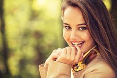 Young  girl smiling in autumn park. Royalty Free Stock Image