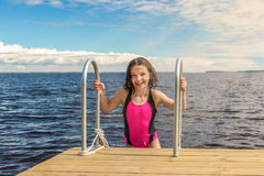 Young cute girl in swimsuit laughing, outdoors on bridge summertime. Royalty Free Stock Images