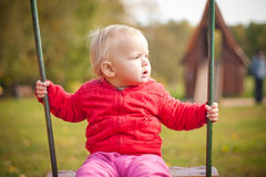 Young cute girl swinging on playground in park Stock Photo