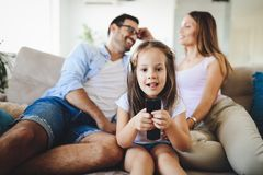 Young girl watching tv with her parents Stock Image