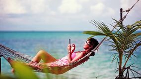 Young cute girl wearing sunglasses lying down in outdoor swing bed enjoying sun sunbathing using mobile phone. 1920x1080 stock video footage