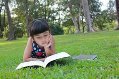 Young cute girls reading. Young cute girls reading in the park Stock Images