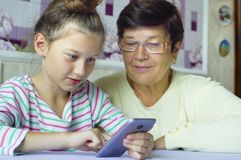 Young cute granddaughter teaching grandmother how to use smartphone at home stock photo