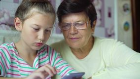 Young cute granddaughter teaching grandmother how to use smartphone at home stock video